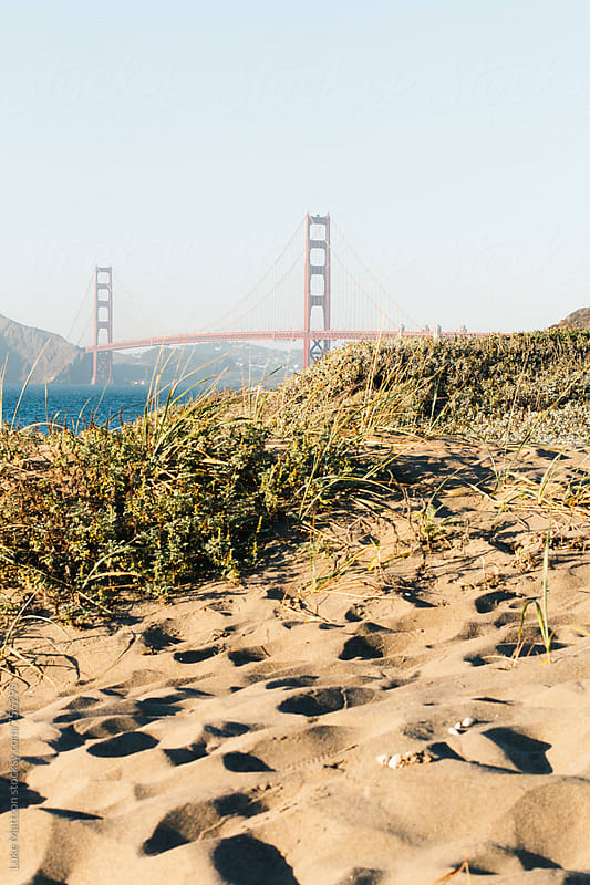 View Of Golden Gate Bridge Above Sand Dune At Baker Beach by Luke Mattson for Stocksy United