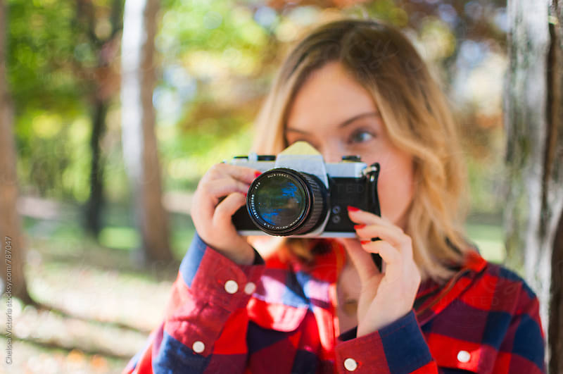 A young woman taking photographs in a forest with a film camera by Chelsea Victoria for Stocksy United