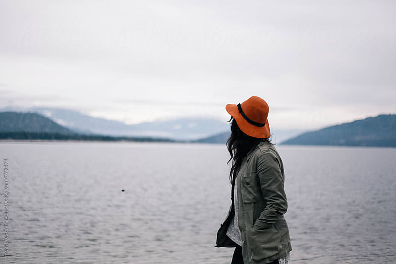 Young woman wearing a hat looking out across the lake by Treasures & Travels for Stocksy United