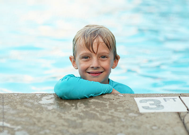 smiling boy at the edge of a swimming pool by Kelly Knox for Stocksy United