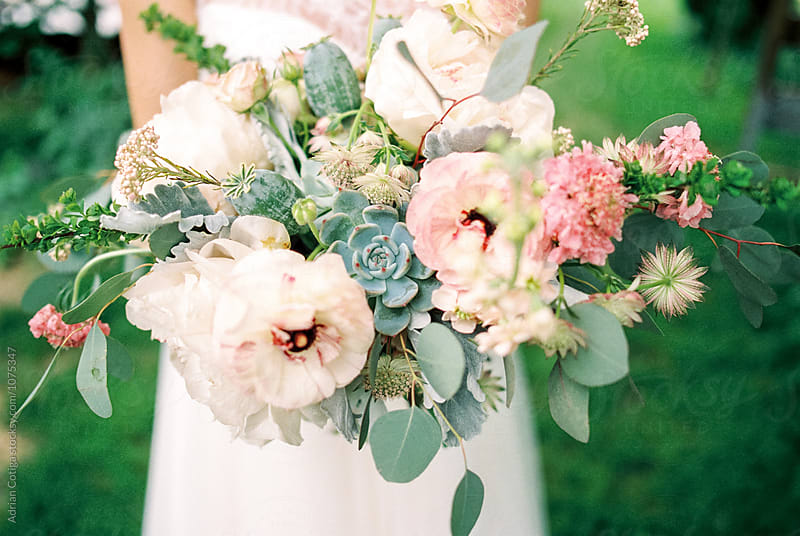 Bridal bouquet; Bride holding the bouquet with succulent flower by Adrian Cotiga for Stocksy United