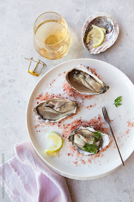 Top view of plate of fresh oysters and bubbly by Nadine Greeff for Stocksy United