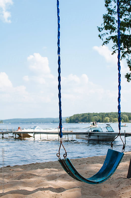 empty swing near a lake by Margaret Vincent for Stocksy United