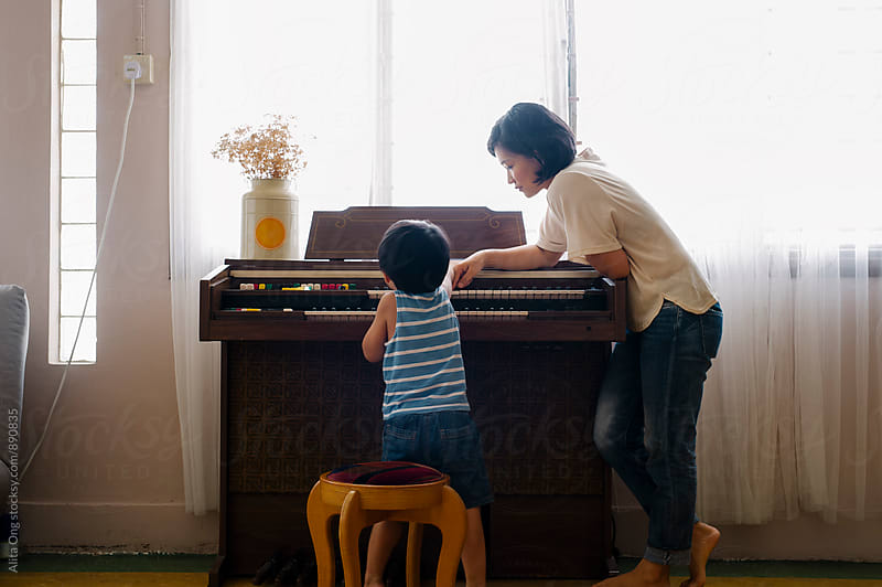 Little boy and his mummy playing piano by Alita Ong for Stocksy United