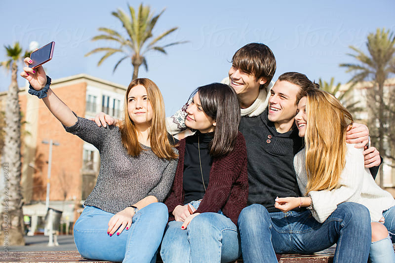 Group of teen friends taking a selfie with their phone outside. by BONNINSTUDIO for Stocksy United