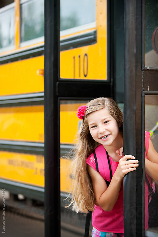 School Bus: Smiling Girl Behind Bus Door by Sean Locke for Stocksy United