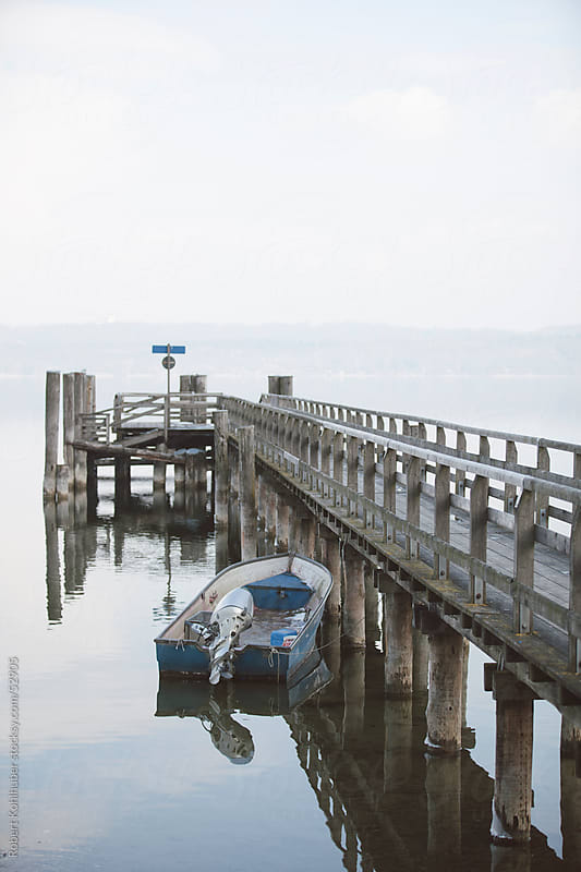Pier at a lake with boat by Robert Kohlhuber for Stocksy United