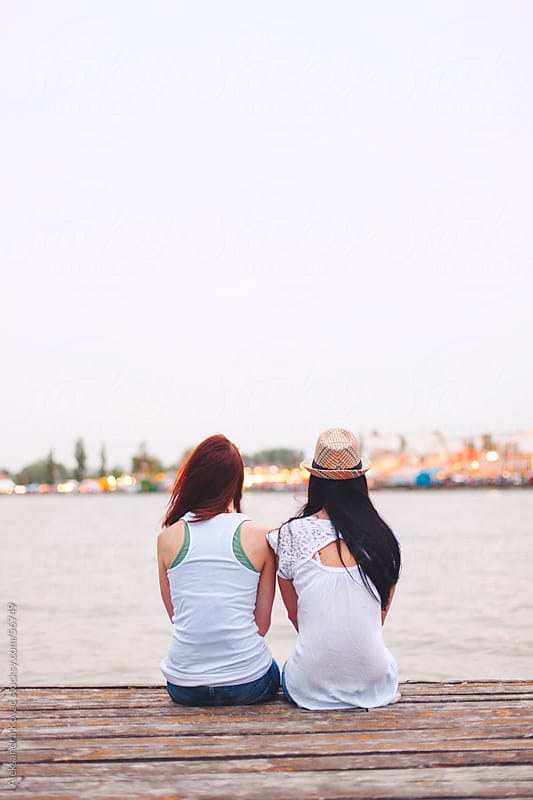 Two young woman sitting on the dock by Aleksandra Kovac for Stocksy United
