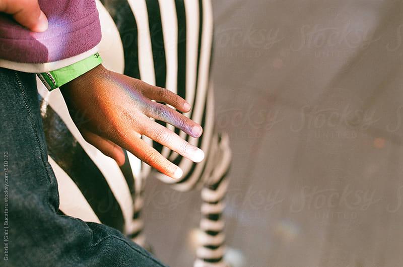 Rainbow on a black girl's hand sitting on a carousel zebra by Gabriel (Gabi) Bucataru for Stocksy United