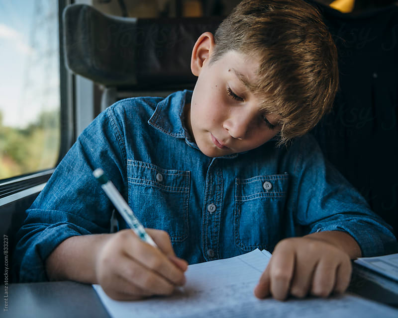 Young boy writing a letter while travelling in train by Trent Lanz for Stocksy United