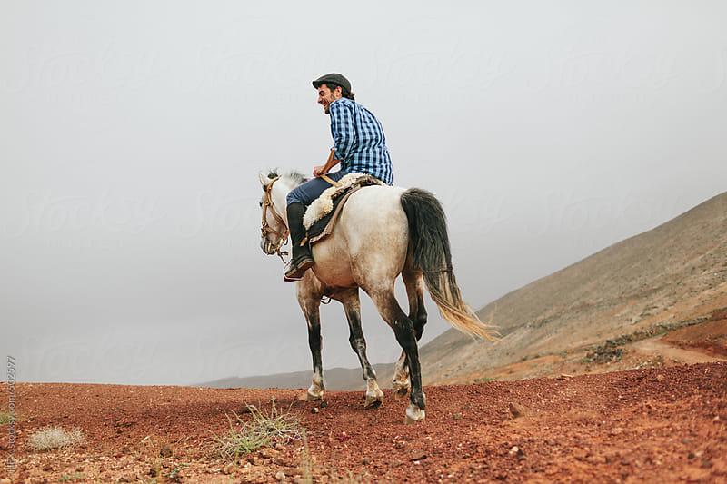 Man Riding a Horse in a Desert Area by HEX. for Stocksy United