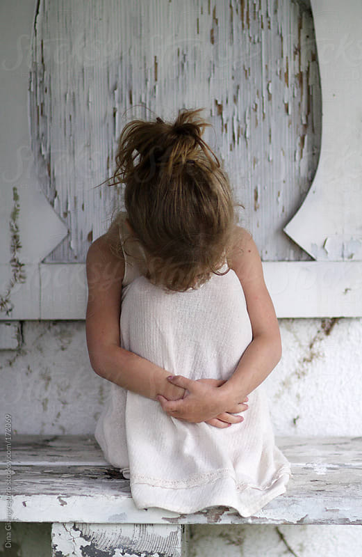 Little girl in white dress hugging her knees sitting on distressed bench by Dina Giangregorio for Stocksy United