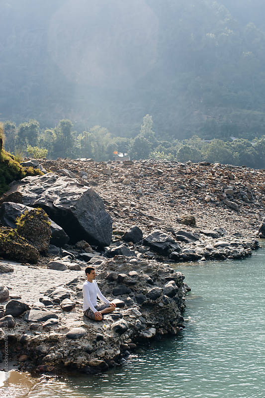 Man Meditating by the Ganges River  by Mosuno for Stocksy United