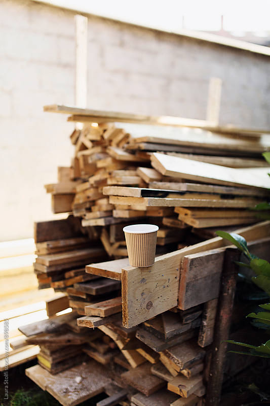 Paper cup on top of wooden planks pile in building site by Laura Stolfi for Stocksy United