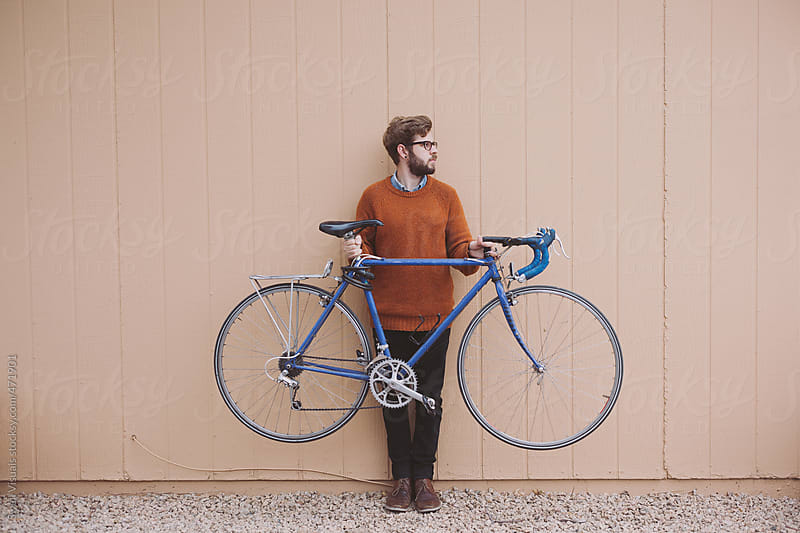 Young Man Holds Bike by Caleb Thal for Stocksy United