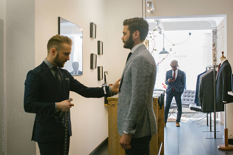 Men's Fashion Store - Black Customer Looking at Smartphone While Tailor Adjusts Suit by VISUALSPECTRUM for Stocksy United