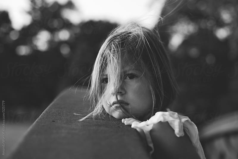 Black and white of a serious young girl with wind blown hair by Amanda Worrall for Stocksy United