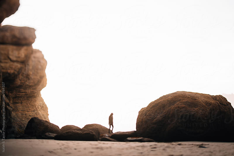Woman walking across rocks soft focus  by Isaiah & Taylor Photography for Stocksy United
