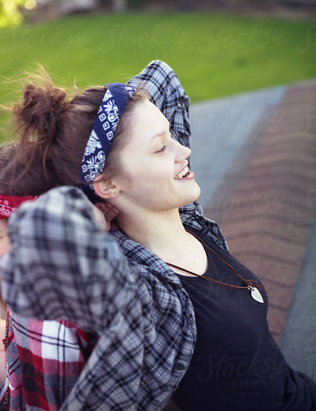 teenager leans back on friend while sitting on rooftop by Tana Teel for Stocksy United