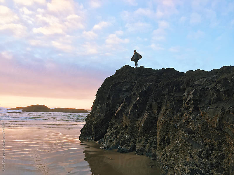 Young Woman Spreading Arms Like Wings On Top Of Rocky Outcrop Along Ocean Shore by Luke Mattson for Stocksy United