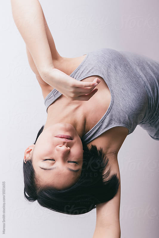 Upside-down portrait of an asian dancer warming up by Maresa Smith for Stocksy United