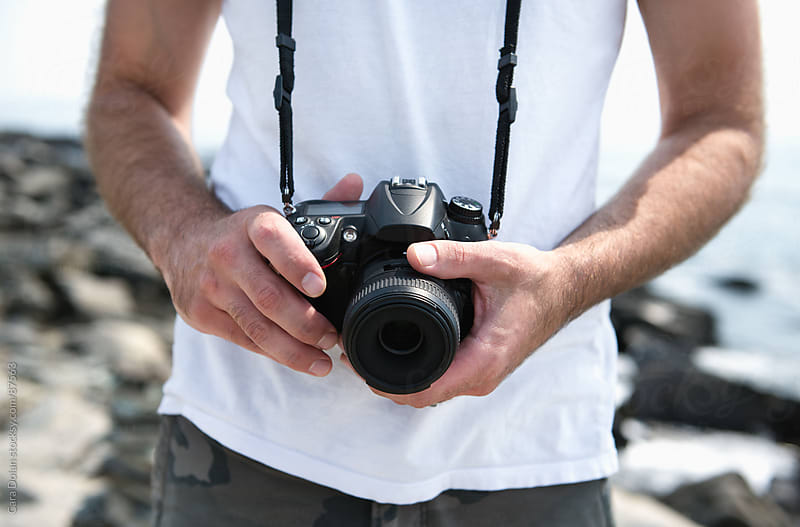 Man at beach uses a digital SLR camera by Cara Dolan for Stocksy United