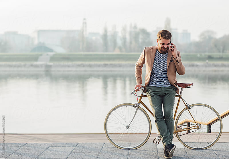 Man With Bike Telephoning by the River by Lumina for Stocksy United