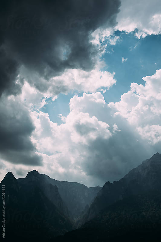 Dramatic sky over mountains by Adrian Cotiga for Stocksy United