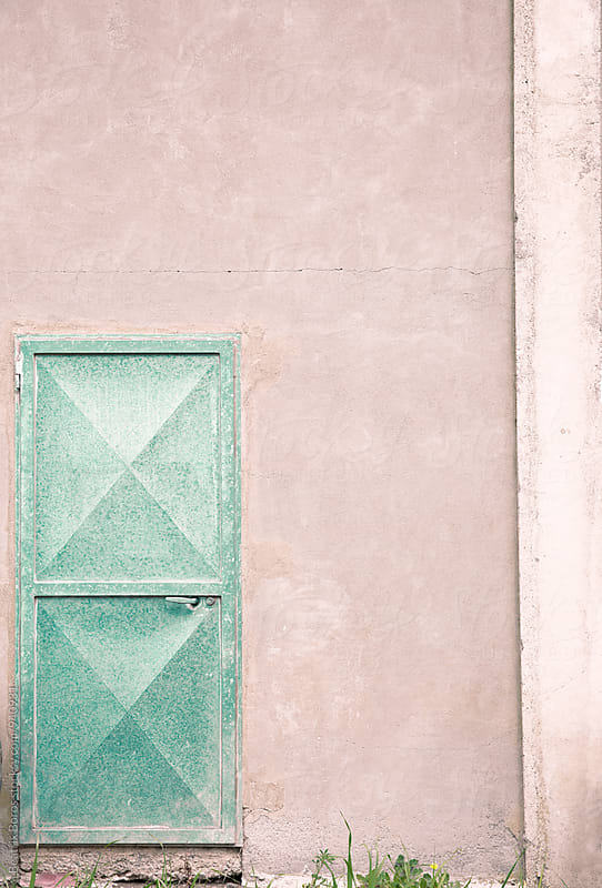 Pastel green rustic iron door on pinkish wall by Beatrix Boros for Stocksy United