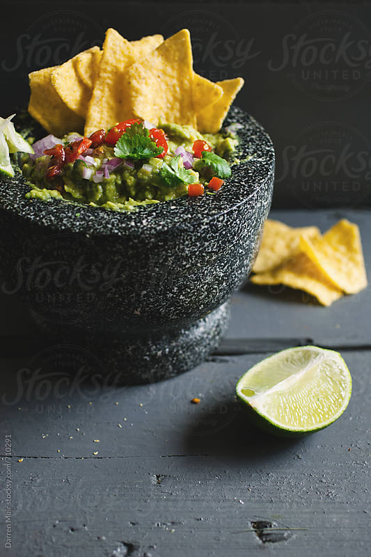 Guacamole and nacho chips snack. by Darren Muir for Stocksy United