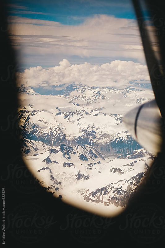 View of Alaskan mountains through a prop plane window by Kristine Weilert for Stocksy United