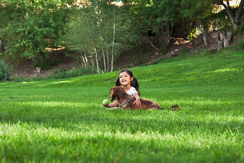 Little girl and dog, playing at park by yuko hirao for Stocksy United