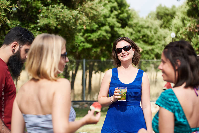 Friends talking at party in garden by Guille Faingold for Stocksy United