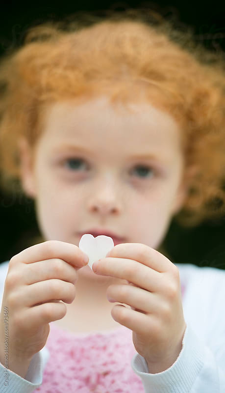 Little girl holding heart shaped petals by Craig Holmes for Stocksy United