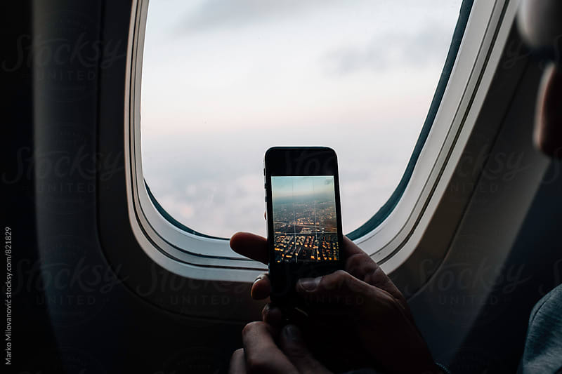 Man taking photos with smartphone from airplane by Marko Milovanović for Stocksy United