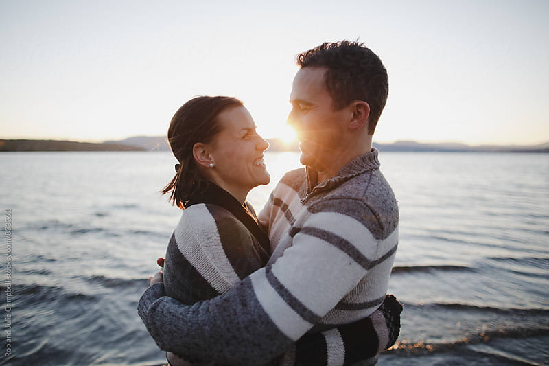 Young happy couple enjoying being together at the beach at sunset by Rob and Julia Campbell for Stocksy United