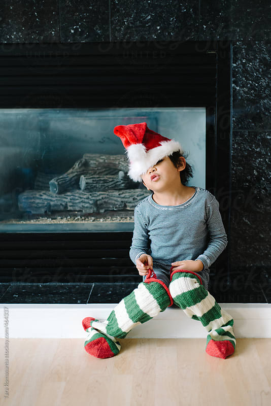 boy wears Christmas stockings and Santa hat  by Tara Romasanta for Stocksy United