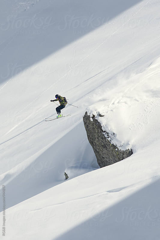 Skier jumping off a snow covered rock