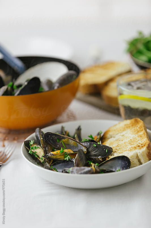Mussels in bowl with crusty bread by Kirsty Begg for Stocksy United