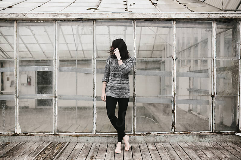 young woman standing on wood platform outside abandoned building  by Nicole Mason for Stocksy United