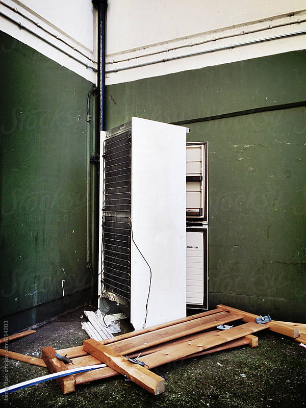 A refrigerator and bed frame in a corner by a building by James Ross for Stocksy United