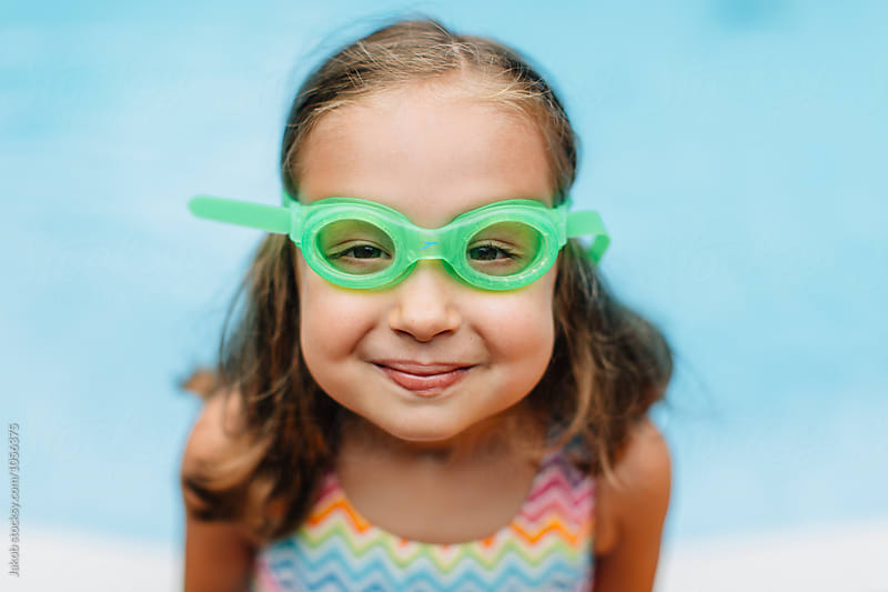 Close up portrait of a cute young girl with swim goggles by a pool by Jakob for Stocksy United