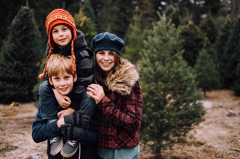 kids posing at Christmas tree farm by Léa Jones for Stocksy United