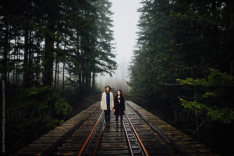 two girls standing in the rain on an abandoned railway bridge by Dylan M Howell Photography for Stocksy United