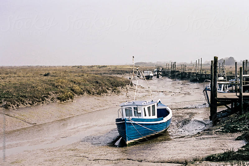 A blue fishing boat at low tide. by Helen Rushbrook for Stocksy United