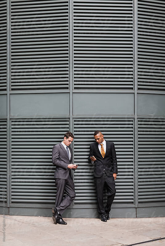 Businessmen using mobile phone by Mauro Grigollo for Stocksy United