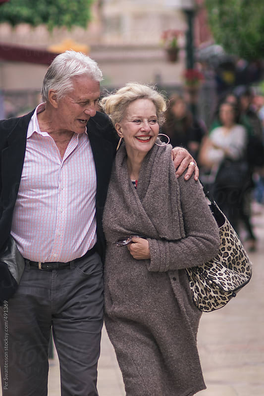 Happy mature couple walking in a city by Per Swantesson for Stocksy United