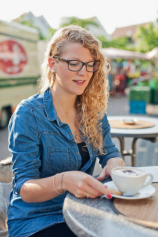 Young woman drinking a cappucino at a farmer's market by Ina Peters for Stocksy United