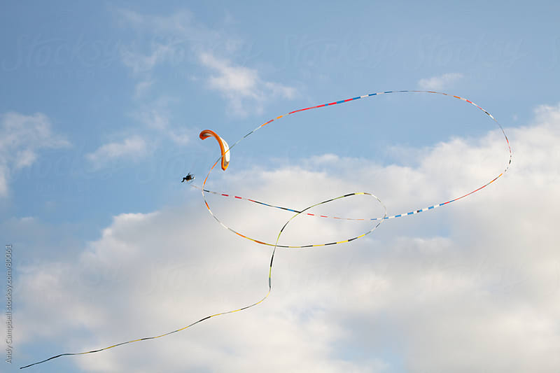 A paraglider flies with a long ribbon streamer by Andy Campbell for Stocksy United