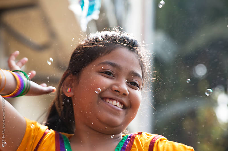 Teenage girl playing with bubbles by PARTHA PAL for Stocksy United